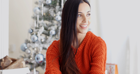 Pretty trendy young woman relaxing over the Christmas season sitting on the floor in the living room in front of the decorated tree smiling at the camera.
